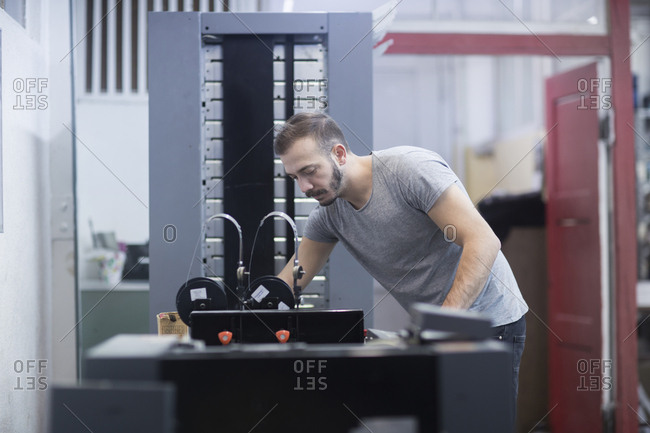 Young man working in printing shop