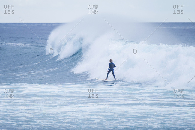 Spain- Tenerife- Teenage boy surfing on sea
