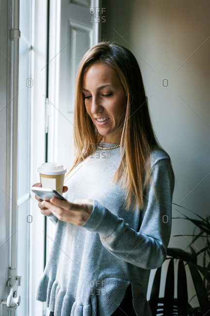 Young woman at the window holding cell phone and takeaway coffee