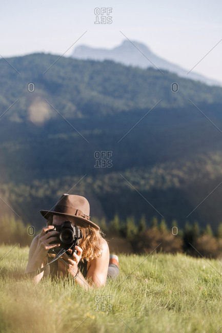 Austria- Mondsee- Mondseeberg- young man lying in meadow taking a picture