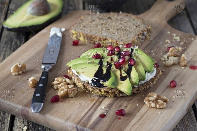 Protein bread slice with cream cheese- sliced avocado- walnuts and  pomegranate seed on wooden board