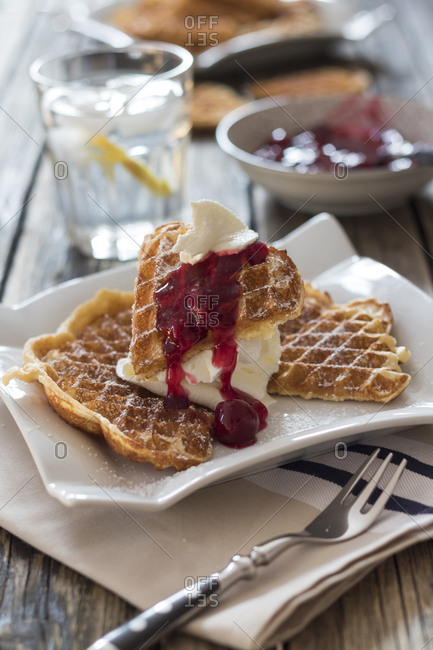 Plate of waffles with whipped cream- cherries and cherry groats