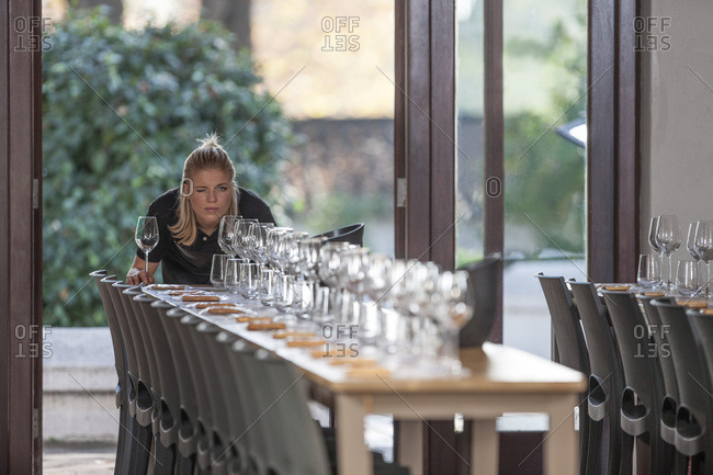 Waitress lining up row of wine glasses at restaurant