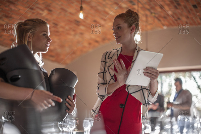 Woman with tablet talking to waitress in a restaurant