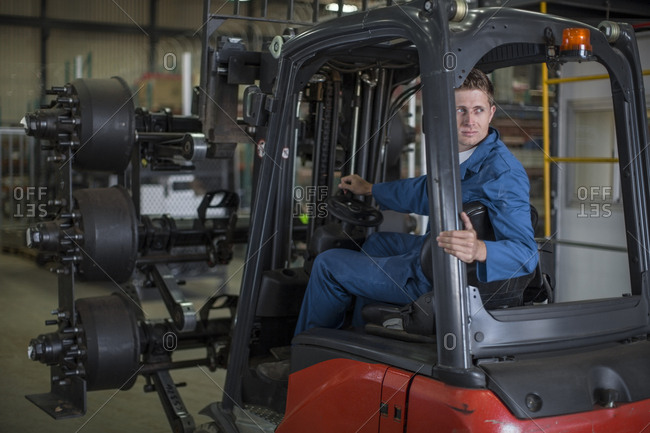 Factory working driving a fork lift in warehouse