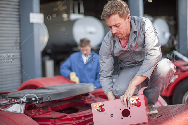 Technician in truck manufacture working on truck container