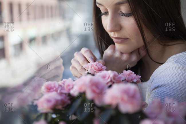 Beautiful woman looking at a flower