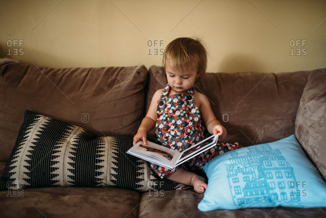 Toddler girl sitting on couch and looking at photo album with photos of her as a baby.