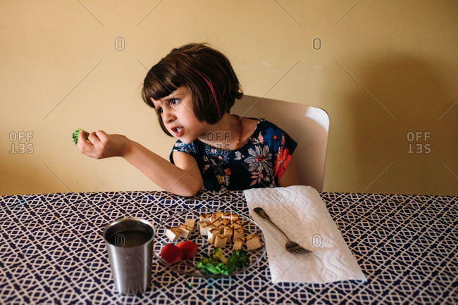 Young girl sitting at a table and making silly faces while eating lunch,