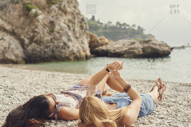 Travelling girls relaxing on beach use smart watch technology on adventure travel trip to connect