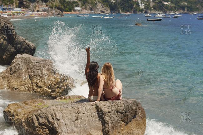 Beautiful carefree girl friends arms raised in bikini on beach sea lifestyle fun summer adventure vacation