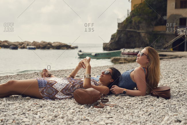 Tourist girls relax on beach using smart phone to connect on adventure travel