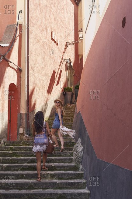 Women travelling in beautiful Italy running up stairs summer vacation exploring to discover european village