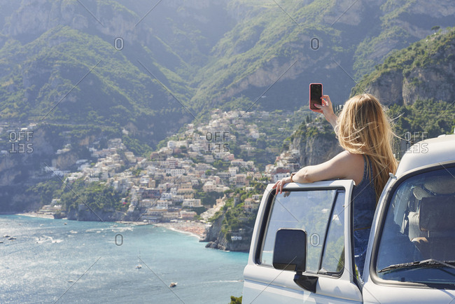 Beautiful girl takes photograph of coast on road trip using smart phone technology for social media while on adventure travel vacation