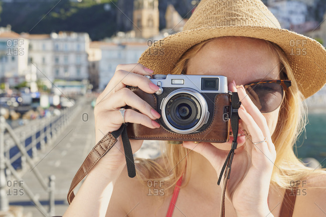 Woman travel in beautiful Italy taking photos vintage camera summer vacation exploring to discover coastal Amalfi