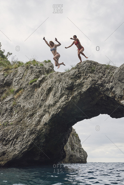 Happy Friends jumping into ocean together having excitement freedom fun action healthy travel vacation adventure