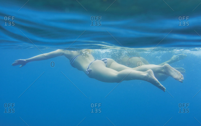Underwater shot of beautiful girl friends jumping into deep blue sea from boat on wild free travel adventure vacation
