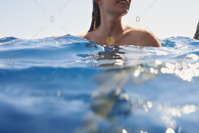 Underwater shot of beautiful girl swimming in deep blue sea from boat on wild free travel adventure vacation
