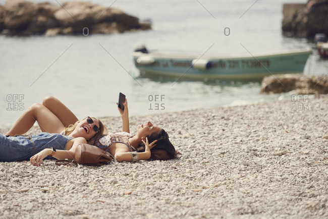 Tourist girls relax on beach using smart phone laughing funny to connect on adventure travel