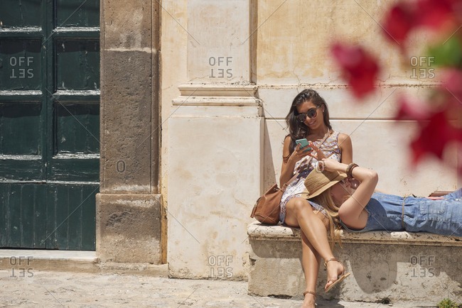Tourist girls relax in European village using smart phone to connect on adventure travel