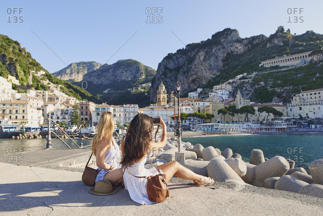 Women travel in beautiful Italy taking photos vintage camera summer vacation exploring to discover coastal Amalfi
