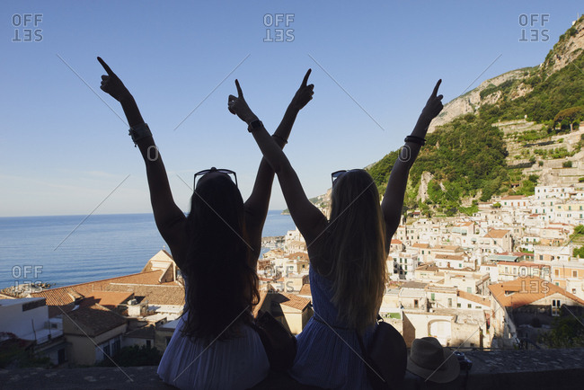Beautiful happy tourist girl friends enjoying scenic view of Amalfi Coast on summer adventure vacation