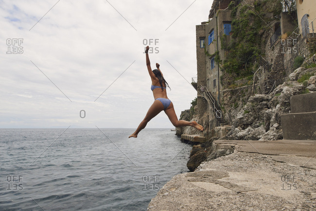 Beautiful girl  jumping into ocean having excitement freedom fun action healthy travel vacation adventure