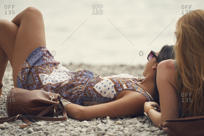 Beautiful girl friends relaxing on beach on travel adventure summer lifestyle