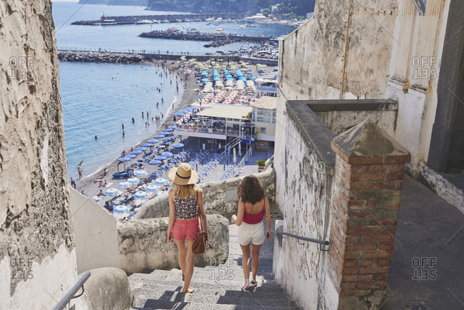 Girl friends travelling in beautiful Italy relaxing summer sea beach vacation exploring to discover carefree lifestyle