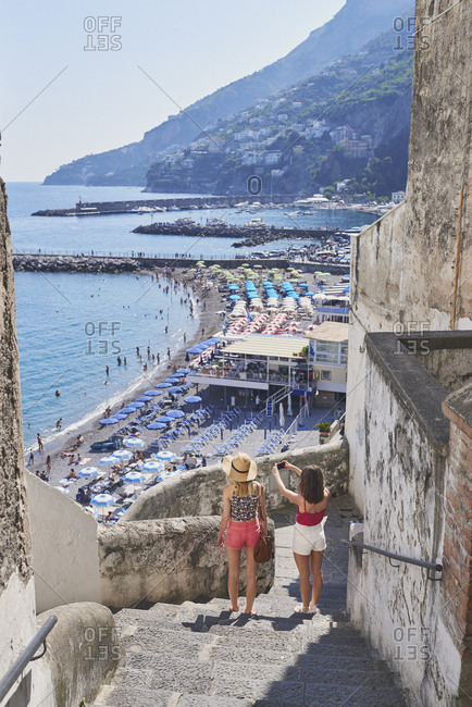 Beautiful girl friends take photographs of Italy coast using smart phone technology for social media while on adventure travel vacation