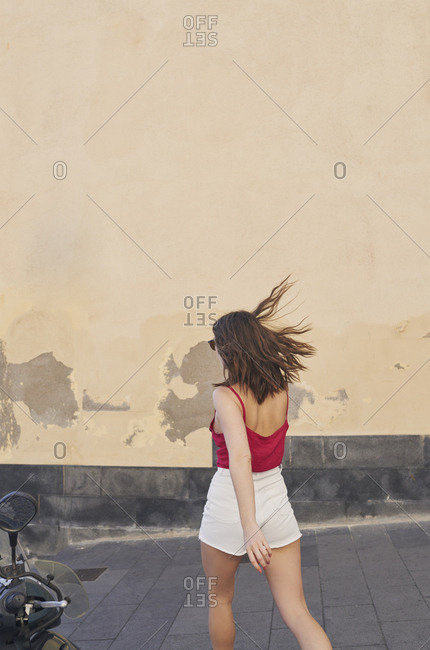 Girl walking in urban street on beautiful relaxing summer vacation exploring to discover carefree lifestyle