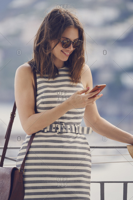 beautiful fashionable woman using smart phone technology at hotel on luxury vacation to communicate on social media
