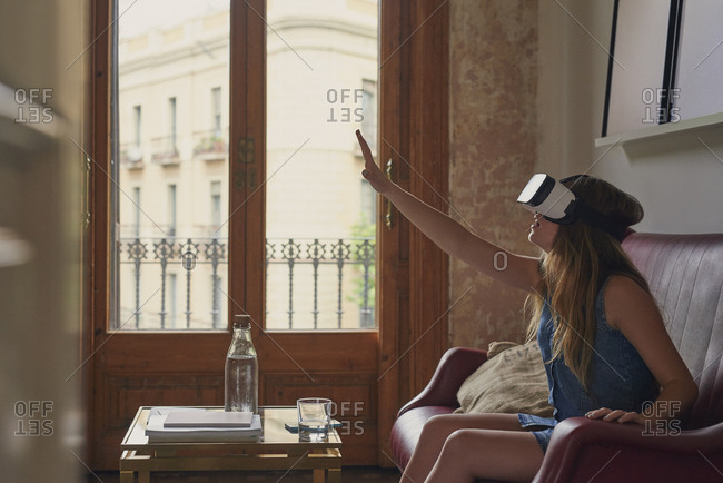 Woman wearing VR headset virtual reality augmented simulator enjoying entertainment at home