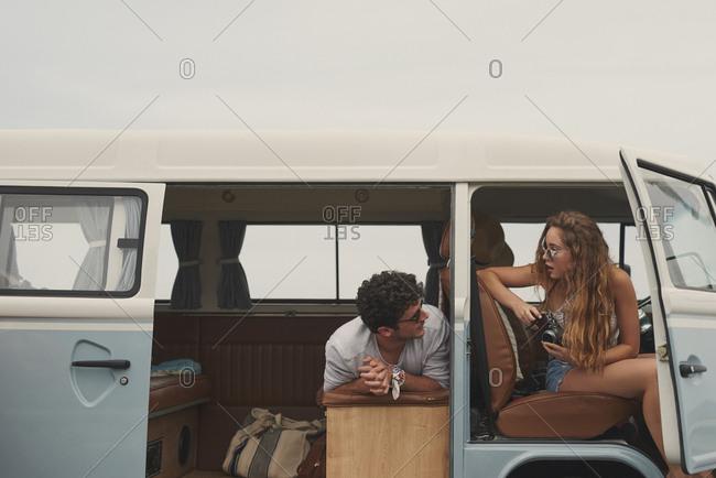 Two friends hanging out in vintage camper van on road trip adventure travel