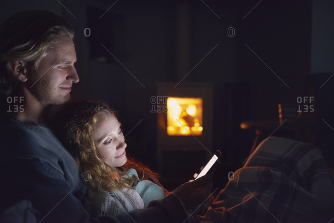 August 1, 2016: Happy man woman couple using smart phone technology cozy at home by fire connection network romance