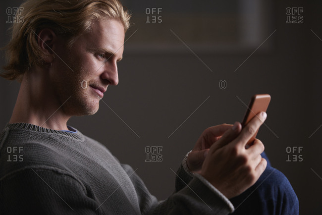 August 1, 2016: Attractive man using smart phone technology at home using social media in internet network