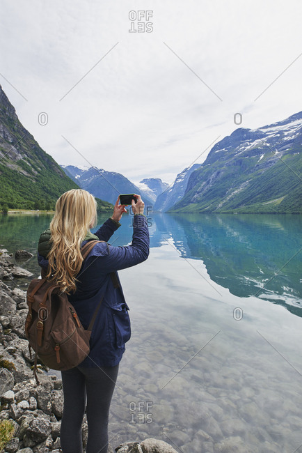 Adventure woman taking photo of beautiful nature mountail lake with smart phone travel explore discover