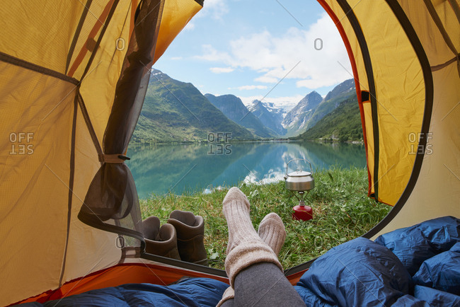 Adventure woman camping at beautiful lake inside yellow tent view of majestic mountain inspiration escape