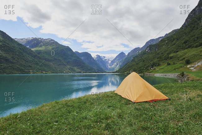 Adventure scene Tent pitched at beautiful lake in view of majestic mountain inspiration wanderlust escape nobody