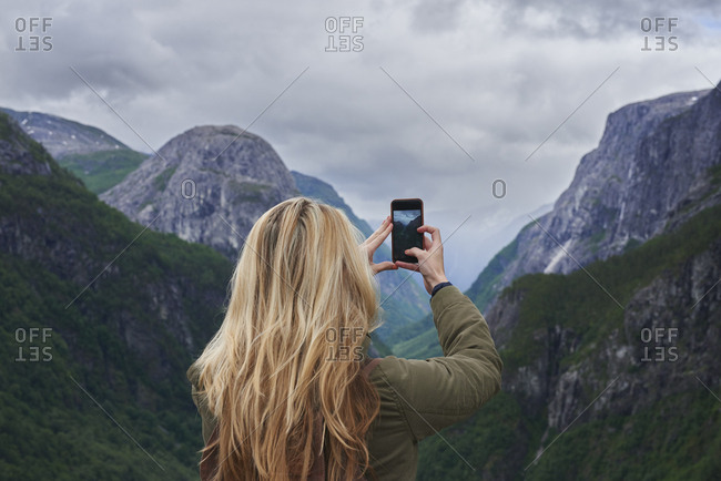 Adventure woman taking photo smart phone of glacial valley landscape on travel exploration for social media