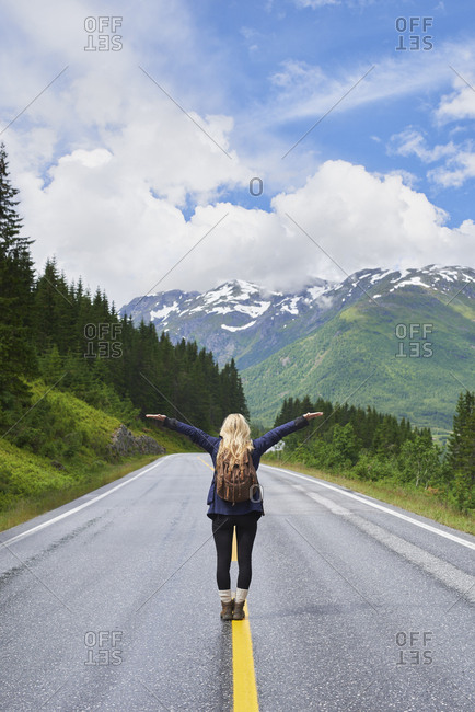 Travel adventure woman celebrates arms raised  at view of majestic road landscape on exploration discover beautiful earth
