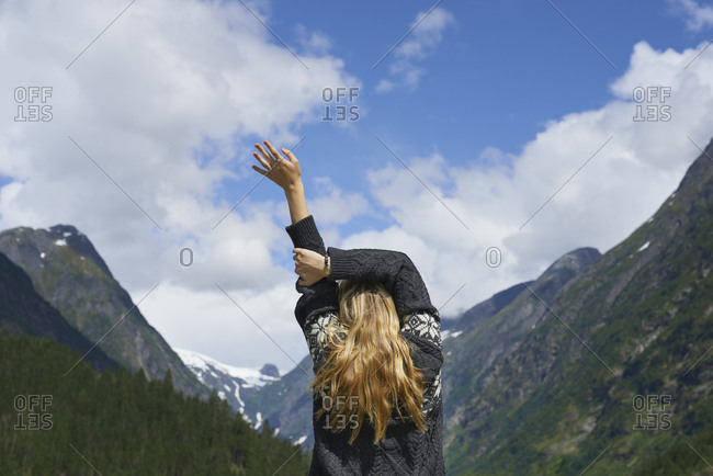 Woman waking up to beautiful view of Mountain stretching healthy alive in nature