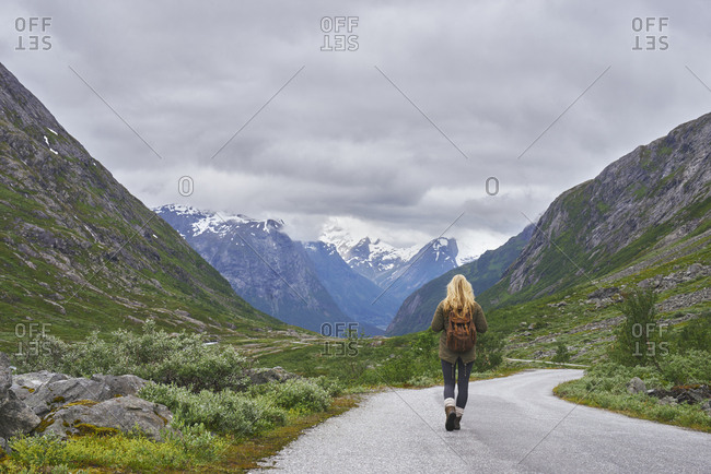 Adventure backpacking woman travels on road in epic majestic mountain snow landscape