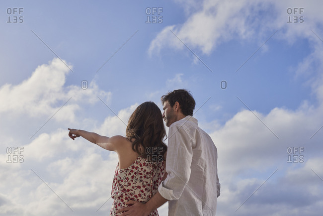 Romantic couple enjoying view together on destination vacation pointing at bright future