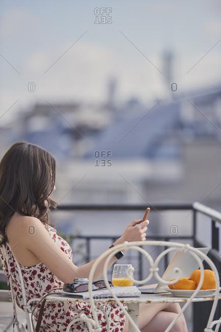 Travel blog woman hotel paris working on vacation laptop smart phone communication on social media