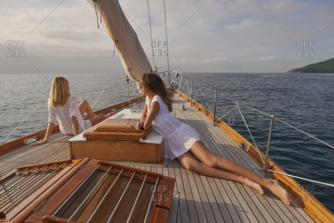 Beautiful girl friends on sailboat at sunset in ocean on luxury lifestyle happy adventure travel vacation
