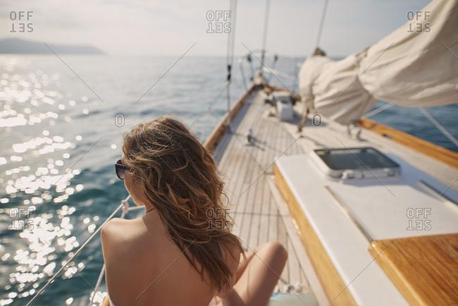 Beautiful woman on sailboat in bikini in ocean on luxury summer lifestyle happy adventure travel vacation