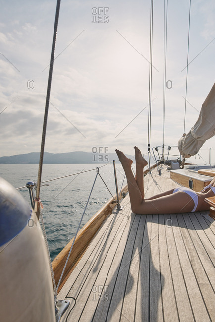 Beautiful sexy woman's legs on luxury sailboat yacht in ocean on lifestyle happy adventure travel vacation in summer