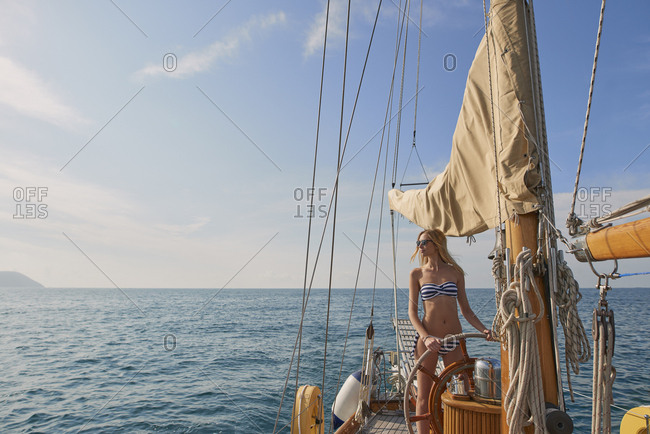 Beautiful sexy woman steering luxury sailboat in ocean on lifestyle happy adventure travel vacation