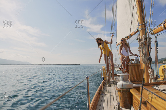Beautiful fashion sexy women steering luxury sailboat in ocean on lifestyle happy adventure travel vacation